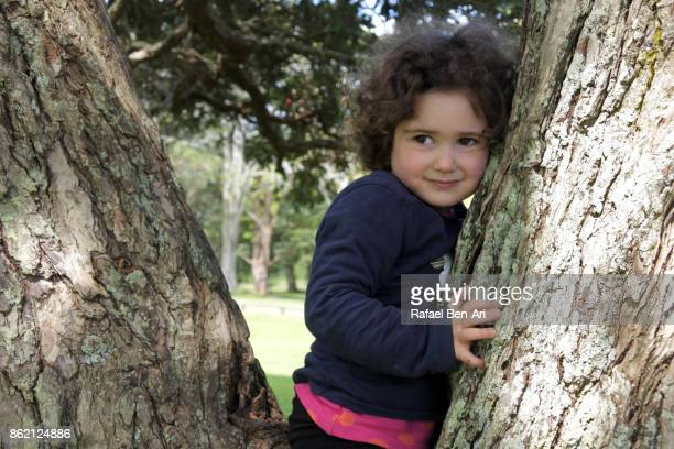 Little girl hides behind a tree