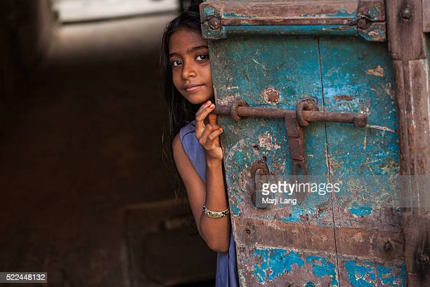 KOCHI KERALA INDIA KOCHI KERALA INDIA Little girl hiding behind a door in the streets of Kochi in Kerala India