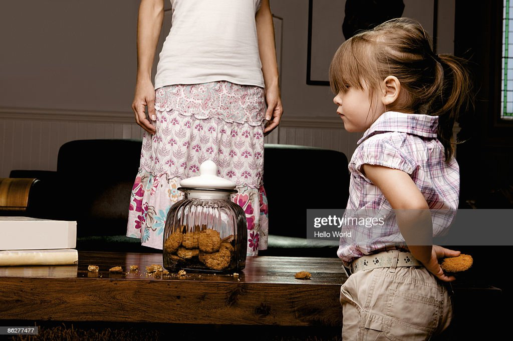 Little girl hiding cookie behind her back : Stock Photo