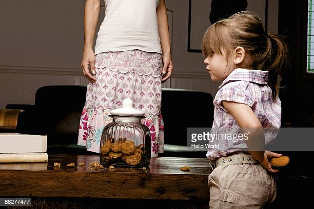 Little girl hiding cookie behind her back