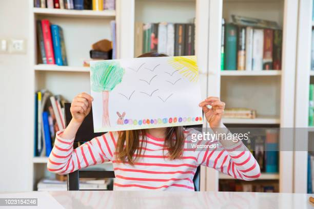 Little girl hiding her face behind her Easter bunny painting
