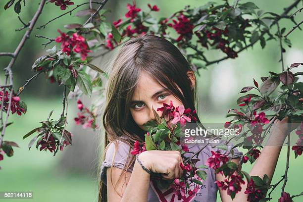 Little girl hiding her face with blossom trees
