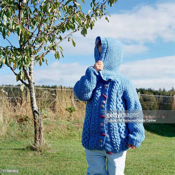 Little girl hiding in cardigan in garden