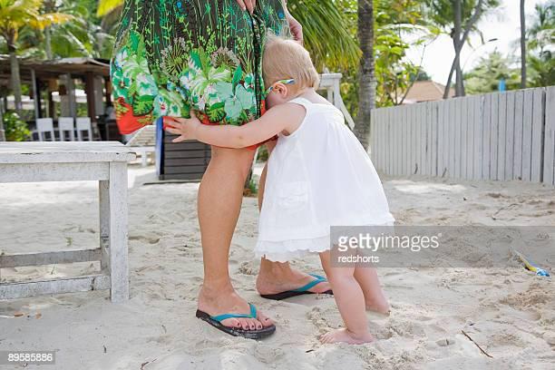 Little girl hiding in mother's legs at beach