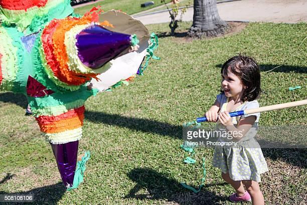 Little girl hitting piñata