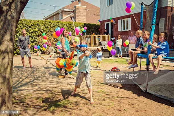 Little girl hitting pinata at birthday party in suburb backyard.