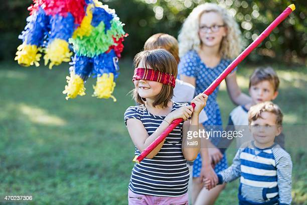 Kleines Mädchen schlagen Piñata in party