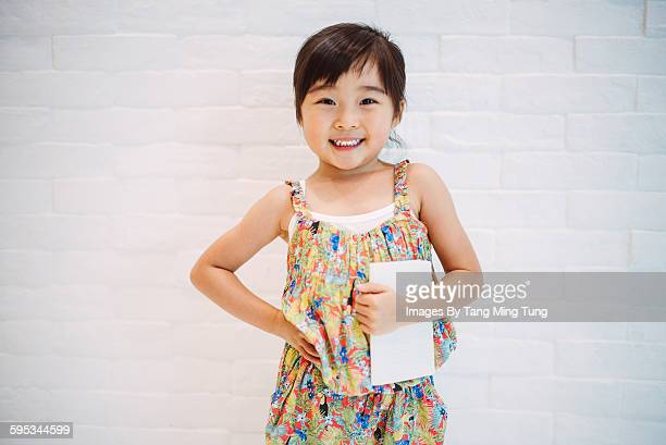 little girl hold a note pad in front of white wall - fringe dress stock pictures, royalty-free photos & images