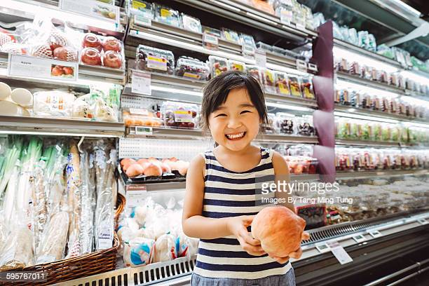little girl holding a big peach in supermarket