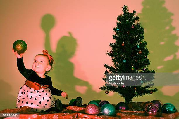 little girl holding a christmas bauble - heshphoto photos et images de collection