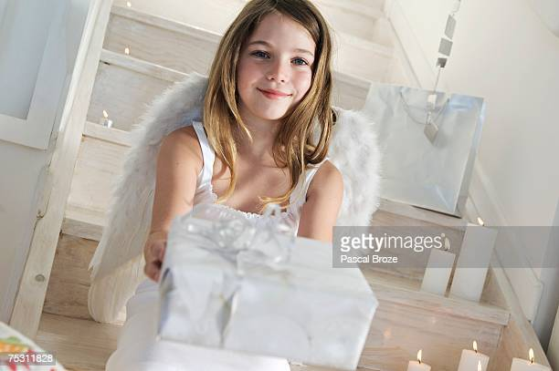 Little girl holding a Christmas present, indoors