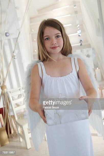 little girl holding a christmas present, indoors - christkind stock-fotos und bilder