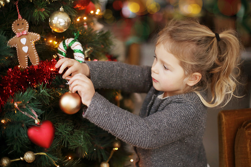 A little girl holding a Christmas tree bauble - gettyimageskorea