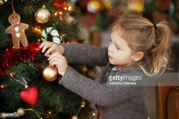 A little girl holding a Christmas tree bauble