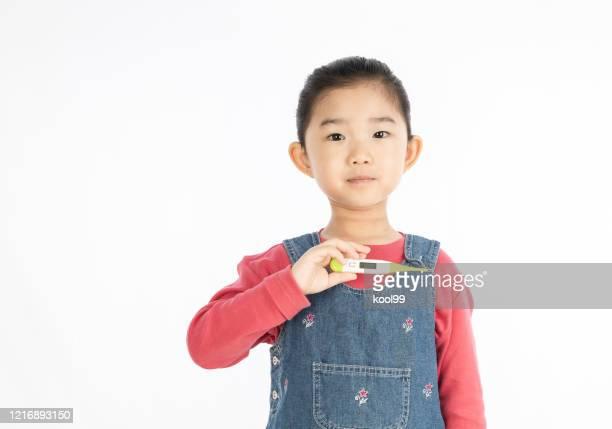 白い背景にデジタル温度計を持っている小さな女の子 - digital thermometer ストックフォトと画像