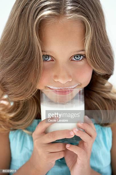 Little girl holding a glass of milk