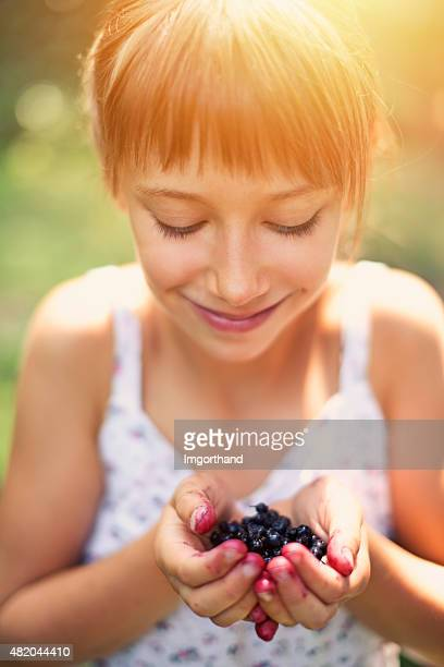 Little girl holding a handful of blueberries