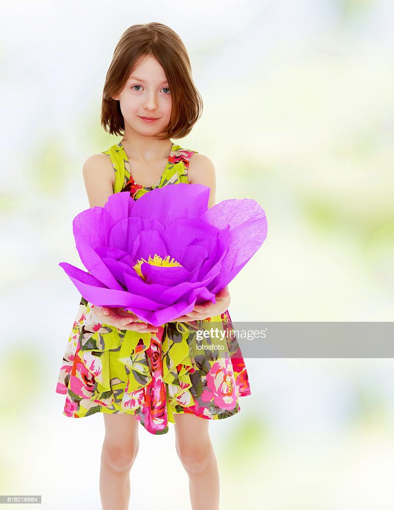 Little girl holding a large purple flower : Stock-Foto