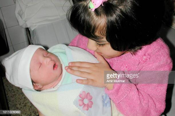 little girl holding a newly born baby boy in her lap - cute pakistani boys stock photos and pictures