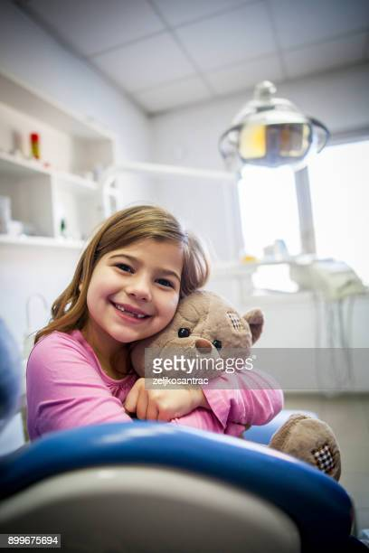 little girl holding a teddy bear in his arms at dentists office - pediatric dentistry stock photos and pictures