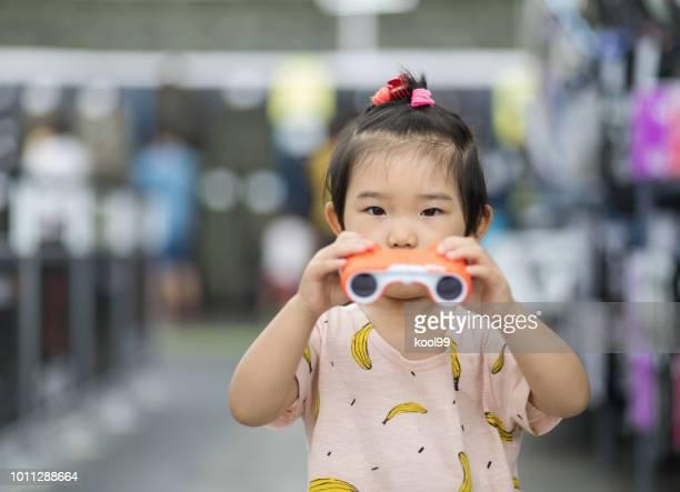 Little girl holding a telescope
