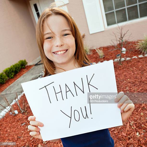 Little Girl Holding a Thank You Sign in Front Yard