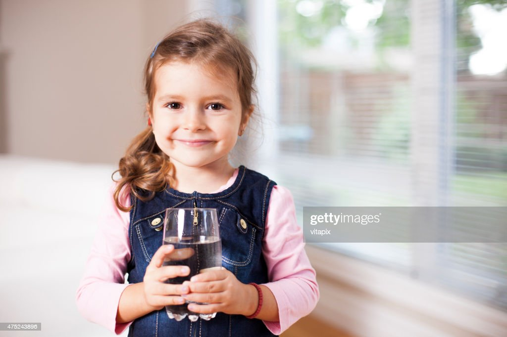 Little girl holding a water glass, looking at the camera : Stock Photo