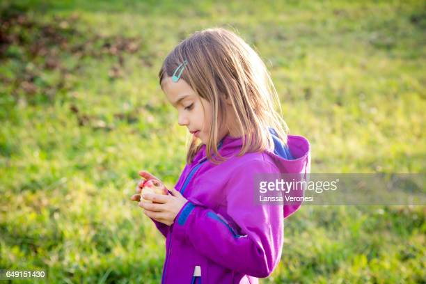 Little girl holding an apple on a meadow in autumn