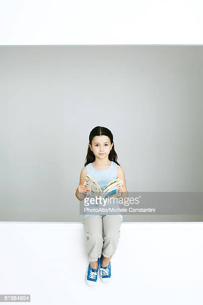 Little girl holding book, looking at camera, full length