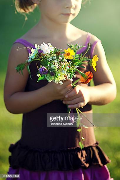 little girl holding bouquet of wildflowers - rebecca nelson stock pictures, royalty-free photos & images