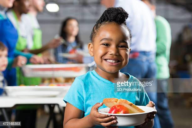 little girl holding bowl at soup kitchen or food bank - charitable donation stock pictures, royalty-free photos & images