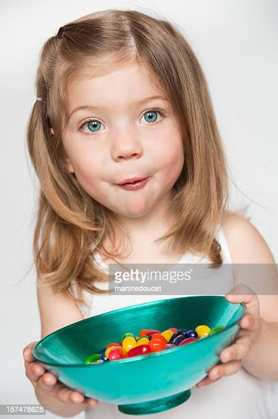 Little girl holding bowl of candy with some in mouth.