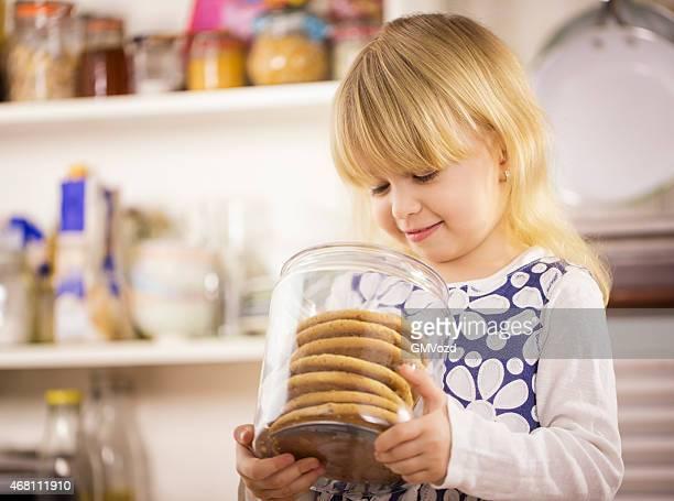 Kleines Mädchen hält Chocolate Chip Cookie in einem Gefäß