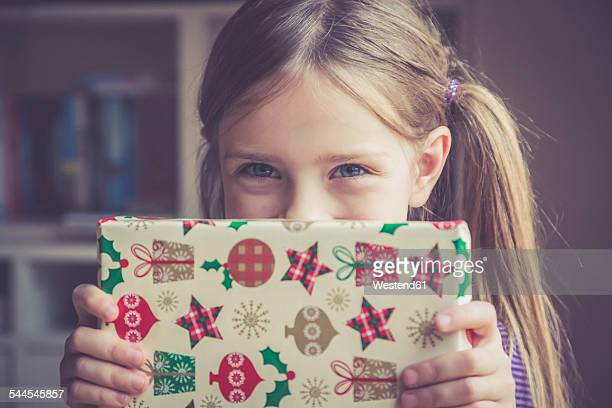 little girl holding christmas present - christmas gifts stock photos and pictures