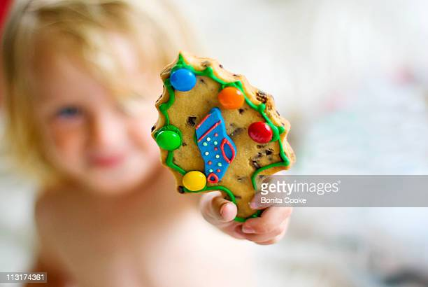 Little girl holding Christmas tree cookie