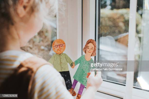 little girl holding cut-out paper people - adoption stock pictures, royalty-free photos & images