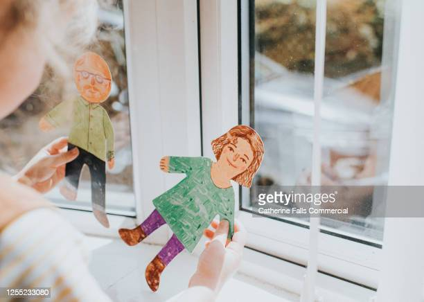 little girl holding cut-out paper people - divorce kids stock pictures, royalty-free photos & images
