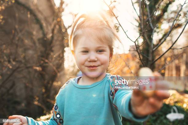 little girl holding easter egg - easter egg hunt stock photos and pictures