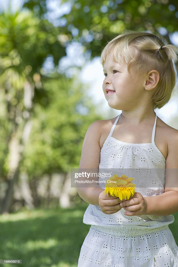 Close Up Of Cute Little Girl Holding Flowers In The Hends