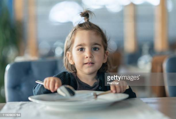 little girl holding fork and spoon with - hungry stock pictures, royalty-free photos & images