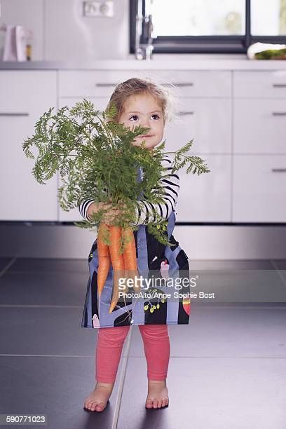 Little girl holding fresh carrots