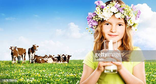 Petite fille tenant un verre de lait sur fond de nature