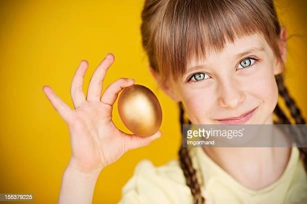 Little girl holding golden egg