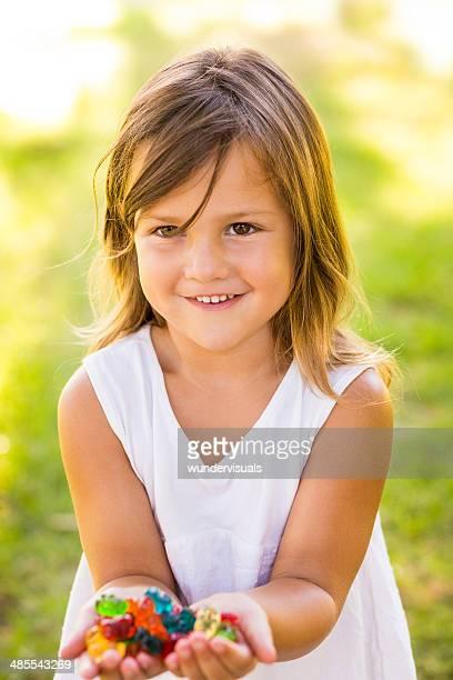 Little girl holding gummy bears