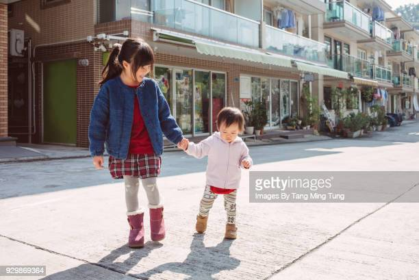 Little girl holding hands with her baby sister strolling around the neighbourhood.