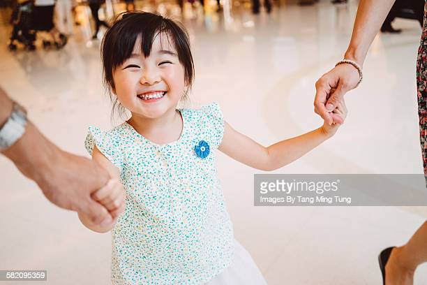 little girl holding hands with mom & dad joyfully
