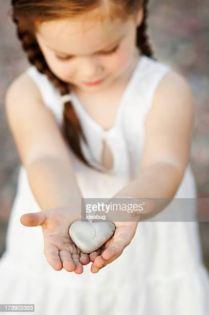 Petite fille tenant coeur en forme de rochers