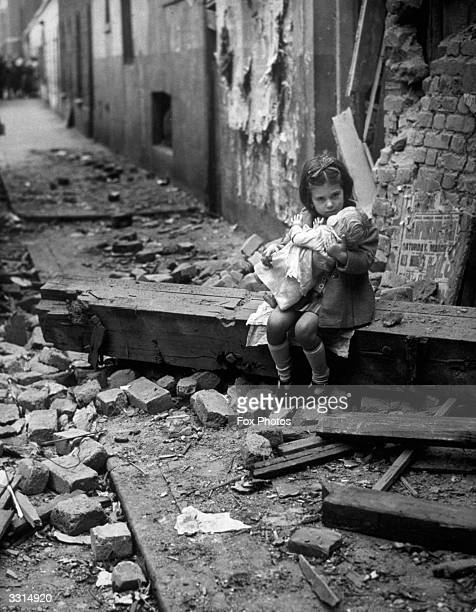 A little girl holding her doll in the rubble of her bomb damaged home
