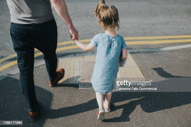 little girl holding her father's hand, about to cross a road - affectionate stock pictures, royalty-free photos & images