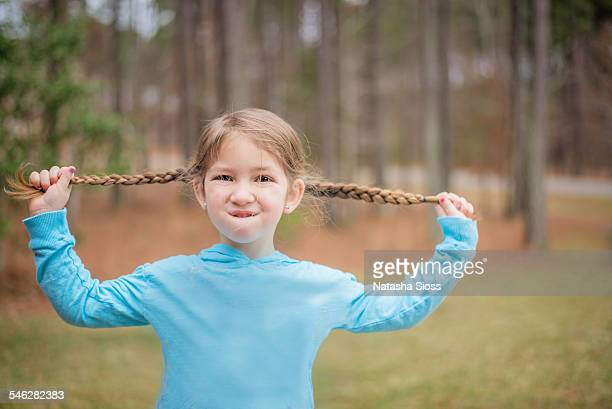 Little girl holding her pigtails